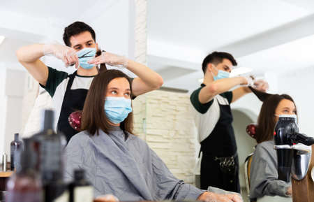 Young man professional hairdresser in mask cut females hair