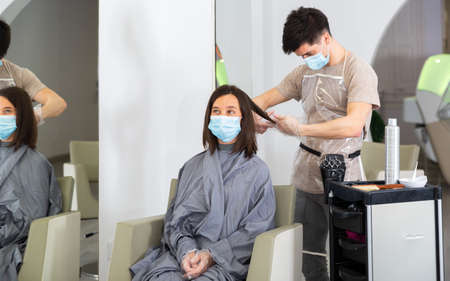 Woman client in mask during cuts hair at beauty salon