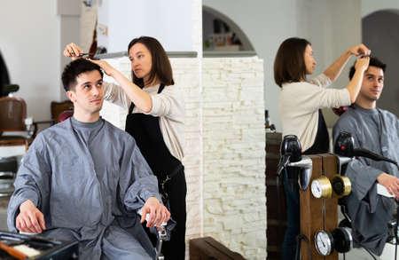Hairdresser cut males hair in hairdressing salon