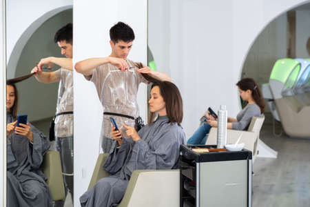 Girl client using phone during hair cut by professional hairdresser 免版税图像