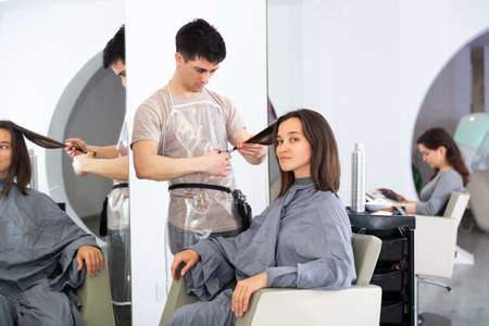 Woman client in during cuts hair at beauty salon