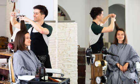 Man professional hairdresser cut females hair in salon