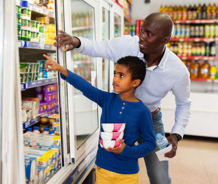 Happy friendly African family of father and tween son shopping together in supermarket