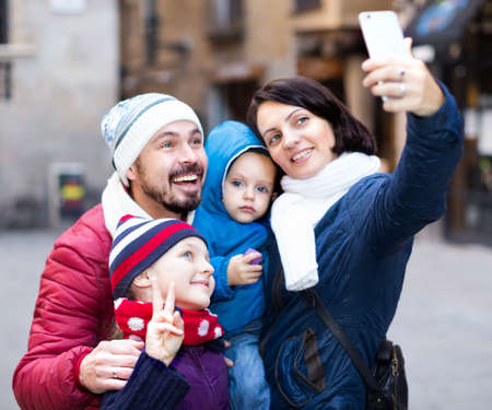 Mother and father with children making selfie