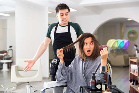 Displeased woman after haircut having conflict hairdresser 免版税图像 - 157984042