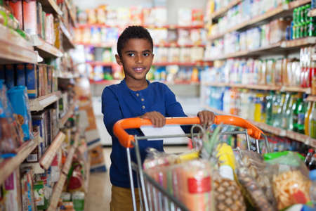 African boy shopping in grocery