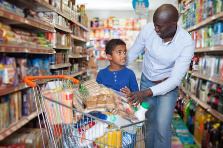 African American man with his son making purchases Stockfoto