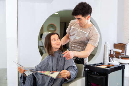 Young woman client with magazine and man professional hairdresser 免版税图像