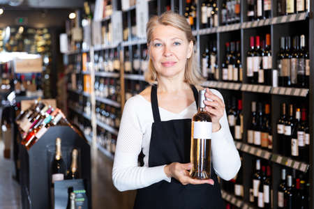 Woman owner of wine store offering bottled wine
