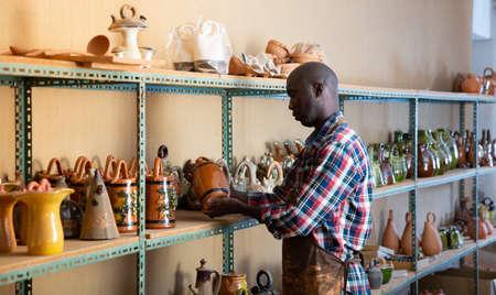 Afro-american artisan in apron having ceramics in store warehouse 免版税图像