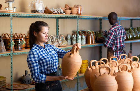 Woman and man artisans in apron having ceramics in store warehouse