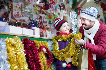Man with daughter choosing decorations for Xmas