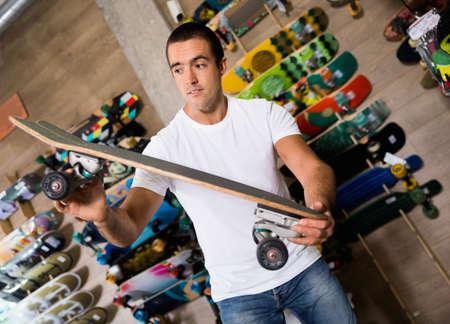 Portrait of man choosing skateboard in sporting goods store