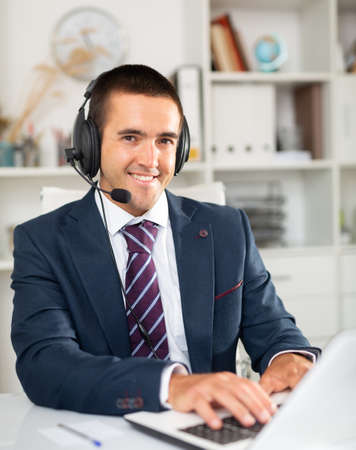 Male operator talking with customer using headset at office Foto de archivo