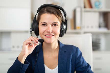 Portrait of smiling woman helpline operator with headphones Imagens