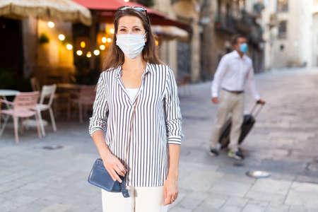 Young brunette in medical mask walking along city street