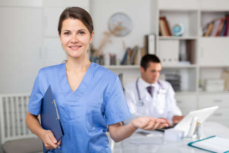 Female doctor making welcome gesture, politely inviting patient in office
