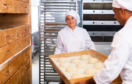 Female baker preparing shaped raw dough for proofing
