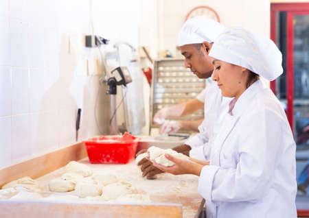 Skilled woman baker forming dough for baking bread