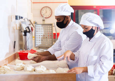 Male and female baker in protective mask working together in bakery