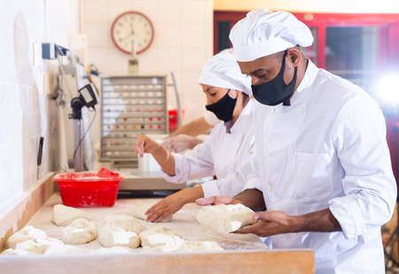 Latin american baker forming bread loaves from raw dough