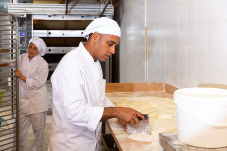 Skilled bakery worker portioning dough and weighing pieces