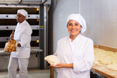 Woman baker smiling at camera during daily work with dough Imagens