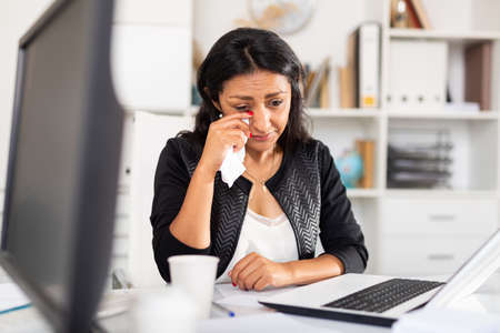 Frustrated female sitting in office with papers and laptop