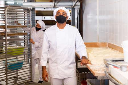 Worker of bakery in protective mask preparing fresh baked goods for sale Zdjęcie Seryjne