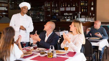 Delighted guests praising hispanic chef in pizza restaurant
