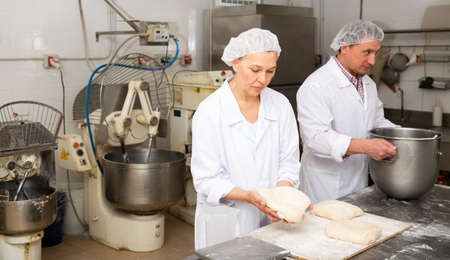 Woman baker forming dough for baking bread