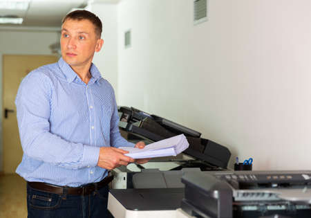 Office worker puts a stack of paper in the printer