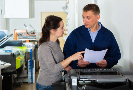 Female designer and print operator working together at the print manufacturing Stock Photo