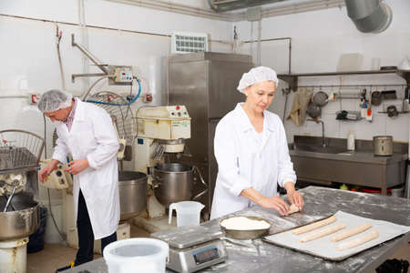 Woman forming baguettes from dough in bakery
