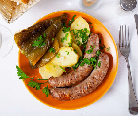Tasty fried pork sausages with baked potatoes and pepper