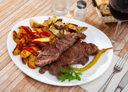Beef steak with potatoes and artichokes on wooden board