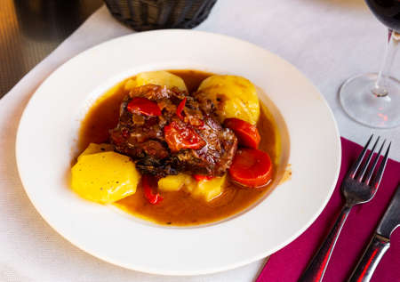 Appetizing lamb shoulder baked with potatoes and stewed vegetables
