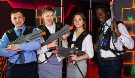 males and females in business suits posing at laser tag room