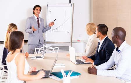 Businessman making presentation on staff meeting Foto de archivo