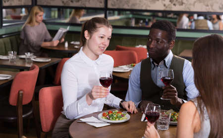 Happy couple with female friend in restaurant Imagens