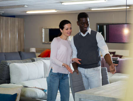 Smiling couple is choosing modern ctable for their home
