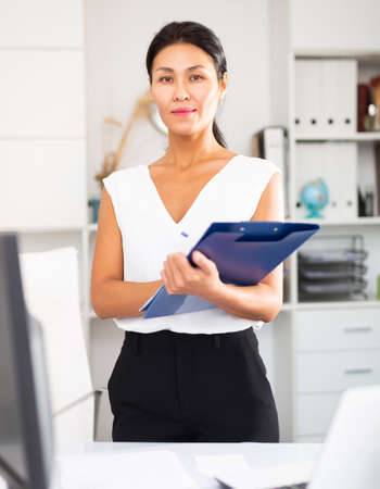 Portrait of female manager with folder of documents in office