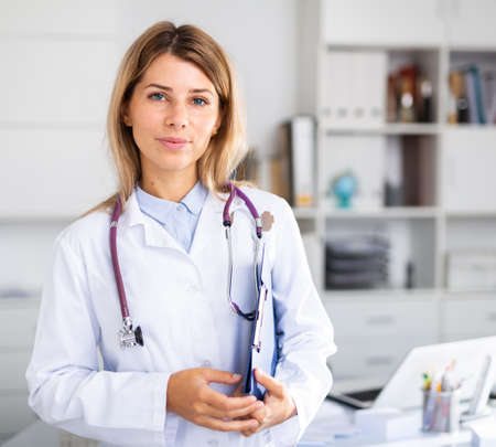 positive female doctor with stethoscope working in cabinet