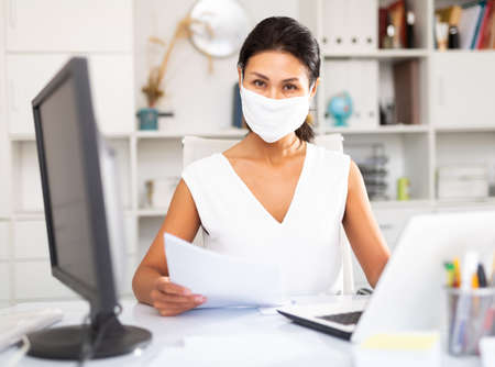 Business woman in protective medical mask using laptop