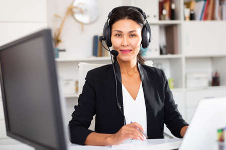 Office worker woman is working at a computer and talking by headset with client in office