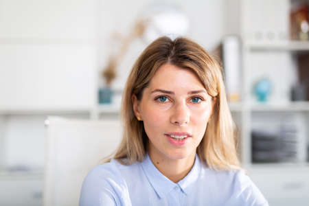 optimistic adult female person posing in white office