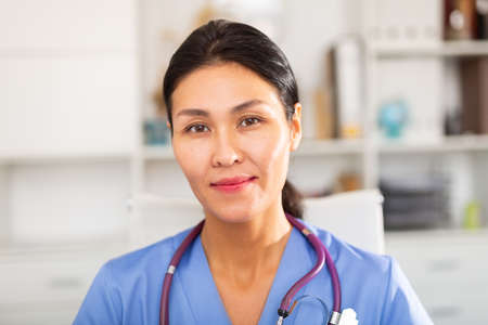 Portrait of positive therapist at computer in medical clinic