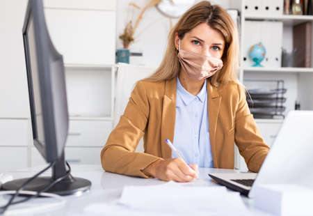 Woman in disposable face mask working in office using laptop