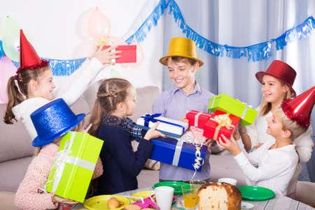 Group of children handing gifts to birthday boy
