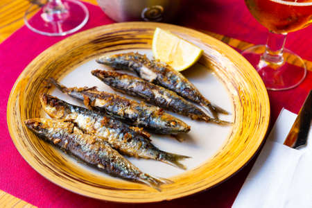 Fried sardines served with slice of lemon